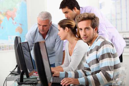 supervisi�n: Los estudiantes maduros en los ordenadores Foto de archivo