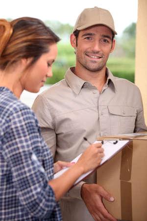 Woman signing for a courier delivered parcel Standard-Bild