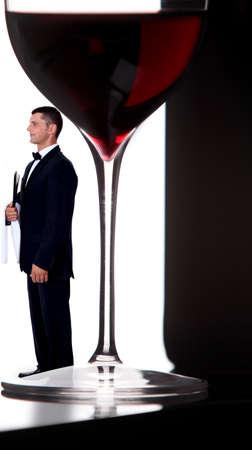 looker: wine steward posing next to giant glass of wine Stock Photo