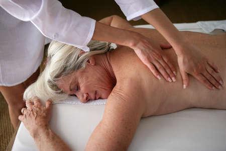 massage herbal: senior woman having a massage