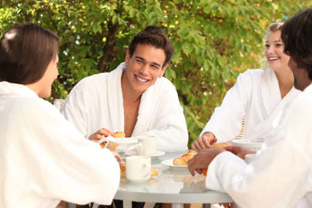 robes: Friends having breakfast together in the garden Stock Photo