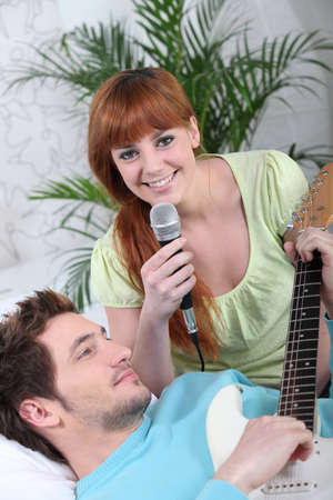 string together: Woman singing and man playing the guitar Stock Photo