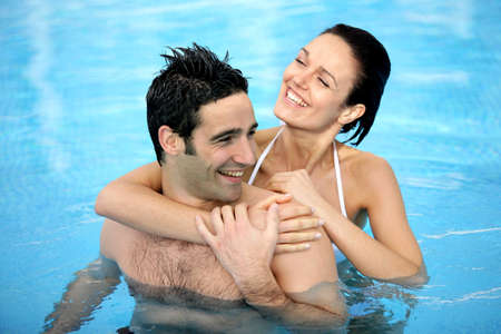 Couple hugging in swimming pool photo
