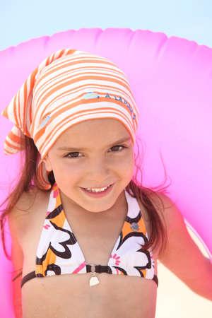 bandana girl: Young girl in a bikini with a pink inflatable beach ring