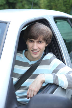 Young man leaning out of car window photo