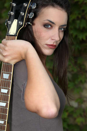 metal music: dark hair woman holding a guitar looked mysterious