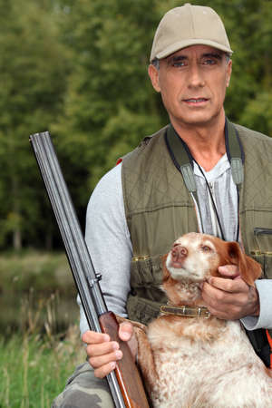 Hunter with a shotgun and dog photo