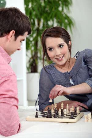 jugando ajedrez: Pareja joven jugando al ajedrez.