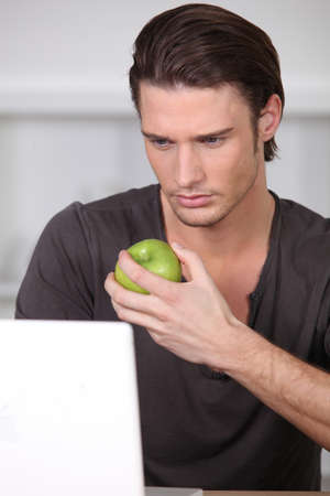 Man eating a green apple whilst using his laptop photo
