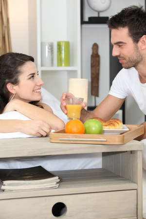 Couple enjoying romantic meal in bedroom photo