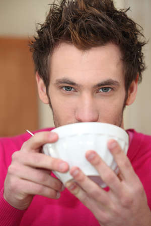 breakfasting: Young man drinking out of a bowl Stock Photo