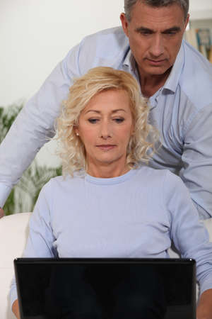 impassive: Couple looking at their laptop