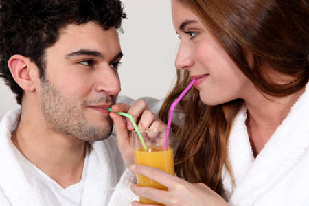 Couple sharing a glass of juice photo