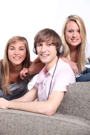 a boy listening music and two blonde girls behind a couch photo