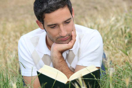 young man lying on the grass and reading a book photo