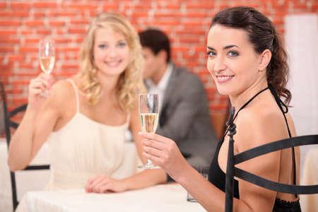 lesbians: dos ni�as vestidas con t�nicas brindando en un restaurante Foto de archivo