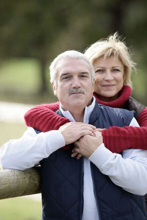 portrait of happy middle-aged couple posing in park photo
