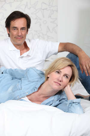 clothed: Fully clothed couple lying on a bed watching television