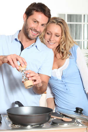 35 39 years: Couple using peppper grinder while cooking in the kitchen