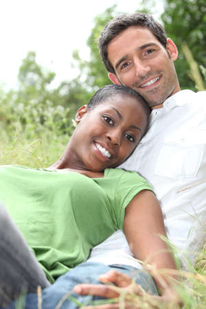 An interracial couple lying on grass. photo
