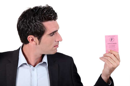 licence: Man looking at driving licence Stock Photo