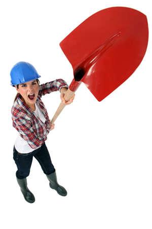 unjust: Expressive tradeswoman holding up a spade
