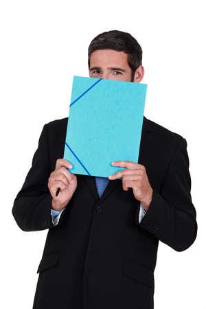 shyness: Smiling man hiding behind a folder