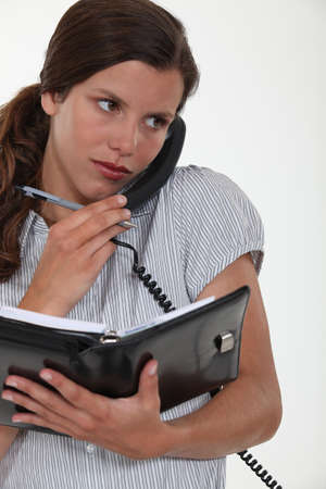 secretary talking on the phone and looking at her agenda Stock Photo - 11757370