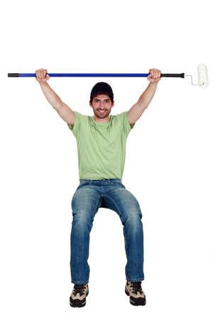 hombre sentado: Comerciante se sienta en un objeto invisible y la celebración de un rodillo de pintura