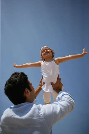 on cloud nine: Man lifting his daughter in the air