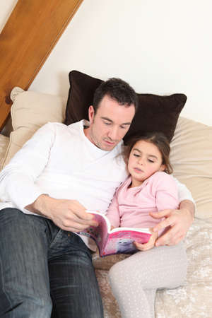 Father reading his daughter a story photo