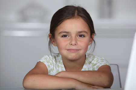 Little girl sat at table photo