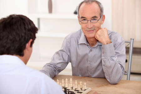 senior playing chess with grandson photo