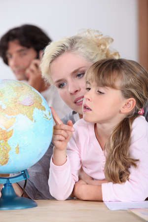 foreign country: a mother is showing to her daughter some country on a globe, her husband is on the phone