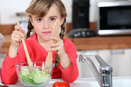 cool kids: young girl cooking salad