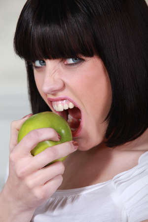 Attractive woman biting into a crisp green apple photo