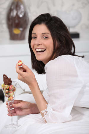 Laughing woman with a glass of mini Easter eggs photo