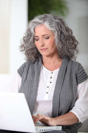 greying: Woman working on her laptop Stock Photo