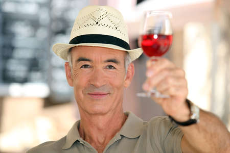 claret: old man raising a glass of claret Stock Photo