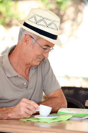 70 year old man: Retired man looking at a map while drinking coffee Stock Photo