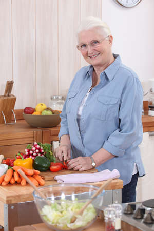 Older woman chopping vegetables photo