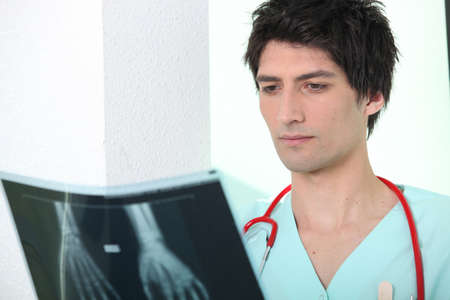 Male nurse looking at x-ray image photo
