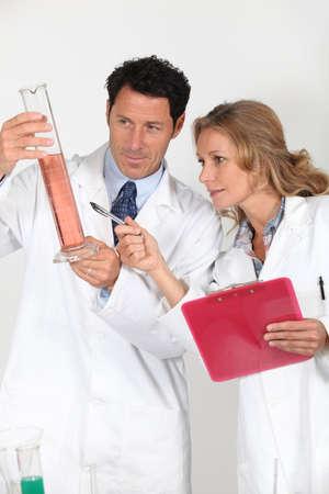 Laboratory technicians examining pink liquid Stock Photo