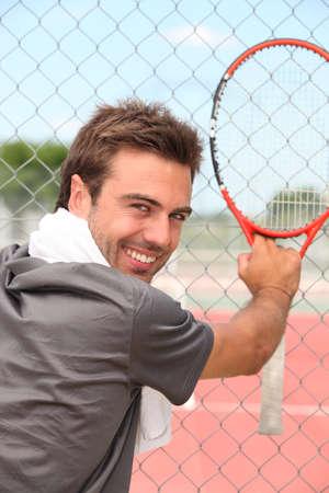 all smiles: tennisplayer all smiles holding racket near court Stock Photo