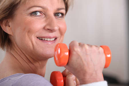50 55 years: Woman lifting dumbbells at the gym Stock Photo