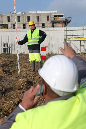 high visibility: Two men measuring construction site