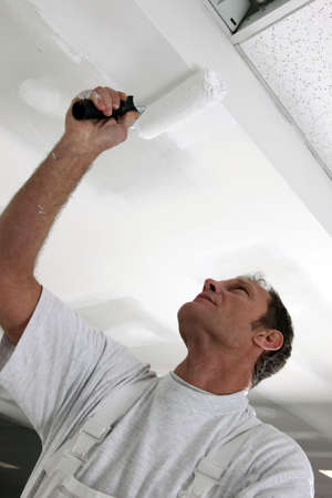Tradesman painting a ceiling photo