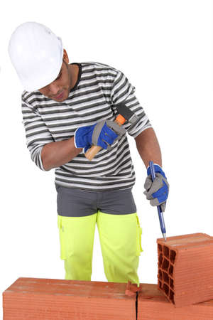 Worker using a hammer and chisel photo