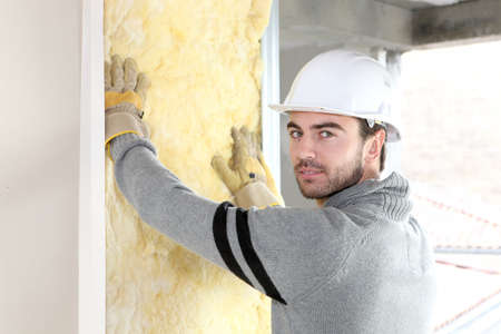 insulation: Worker installing new insulation Stock Photo