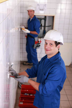 Two electrician working on restroom photo